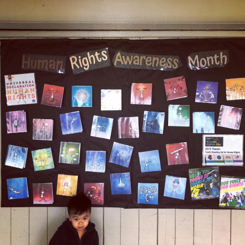 "Toddler standing in front of a school bulletin board titled ""Human Rights Awareness Month"""